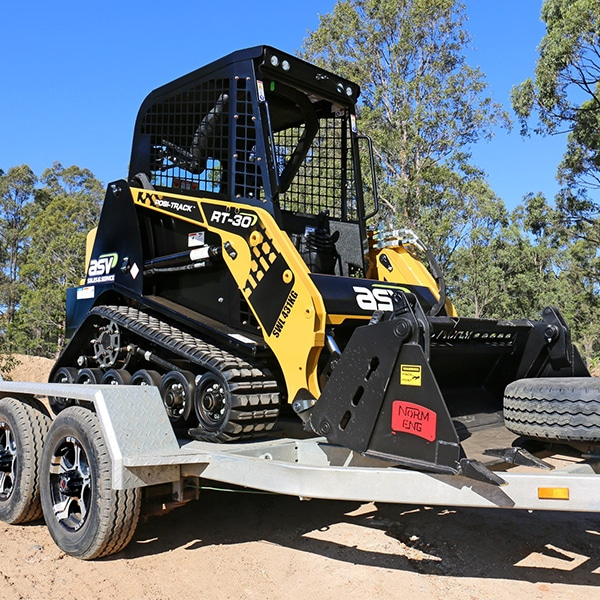 Small track loader on trailer